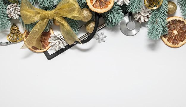 Sfondo di natale medico con stetoscopio, clip board e alberi di natale con palline e campane