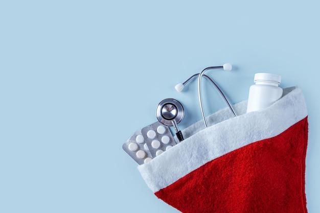 Composizione medica in natale con pillole, vasetto di vitamine e stetoscopio in cappello rosso di babbo natale sull'azzurro