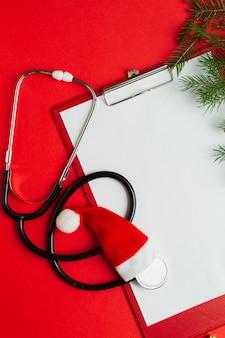 Concetto medico di natale con appunti in bianco dello stetoscopio con carta bianca