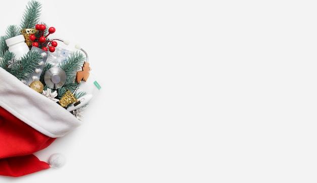 Banner piatto di natale medico con cappello da babbo natale e uno stetoscopio, pillole, termometro e decorazioni di capodanno su sfondo bianco con spazio di copia.