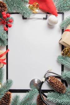 Piatto di natale medico laici con clip board e stetoscopio è incorniciato con decorazioni di capodanno. copia spazio