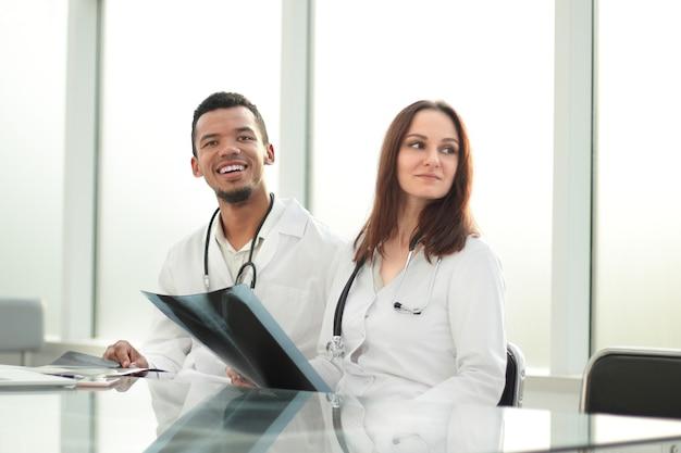 Colleghi medici con raggi x seduto alla scrivania in ufficio.