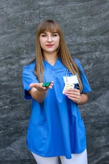 Concetto medico. la bella giovane infermiera in uniforme blu tiene le pillole.
