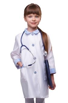 Concetto medico. medico sorridente sveglio della bambina che porta il camice bianco con lo stetoscopio tiene la cartella su fondo isolato bianco