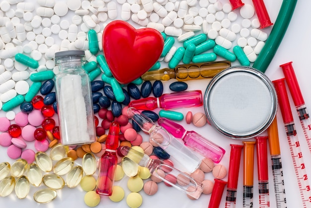 Concetto medico - pillole, stetoscopio, fiale, siringhe e cuore