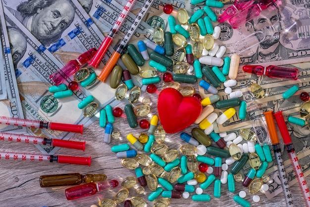 Concezione medica su fondo di legno con dollari, compresse e siringhe