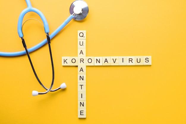 Parole incrociate e phonendoscope medici su una priorità bassa gialla. concetto di quarantena pandemica