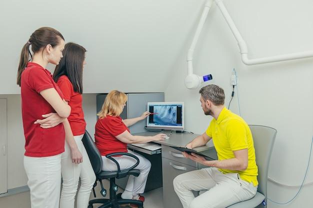 Il team di medici dentisti in studio dentistico discute ed esamina l'immagine dei raggi x guardando il computer