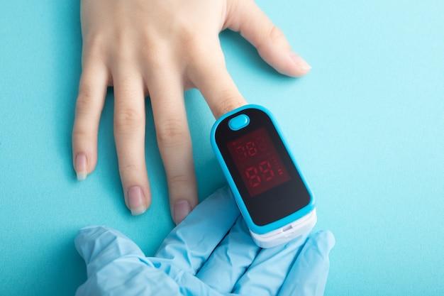 Dispositivo medico per misurare la saturazione di ossigeno nel sangue. il medico misura il paziente su uno sfondo blu