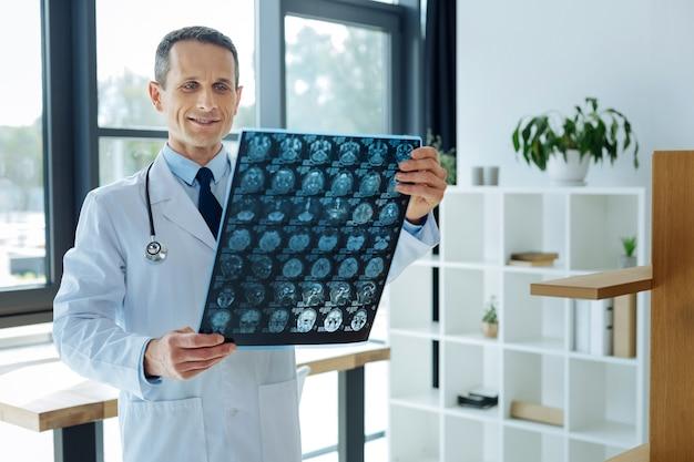 Diagnosi medica. serio neurologo professionista intelligente che tiene una scansione a raggi x e lo guarda mentre fa una diagnosi