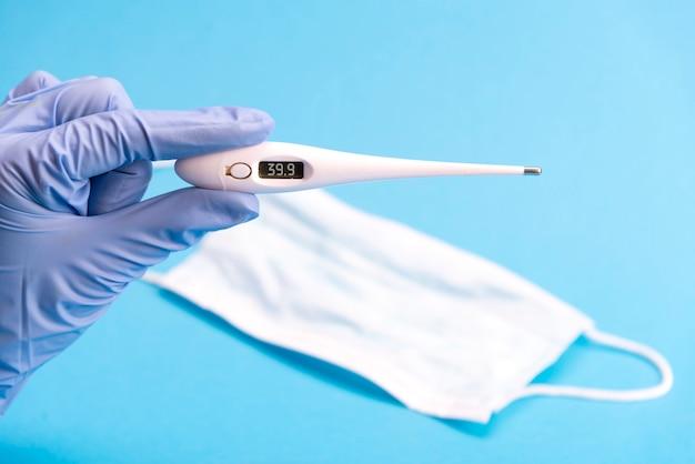 Termometro digitale medico e mascherina medica su una priorità bassa blu. concetto medico