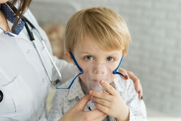 Medico che applica il trattamento di inalazione di medicina su un bambino con terapia d'inalazione di asma dalla maschera dell'inalatore.