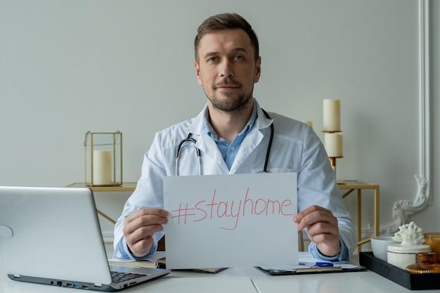 Medico in possesso di un cartello di soggiorno a casa durante un'epidemia di coronavirus