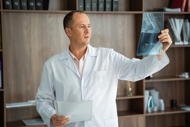 Medico che esamina un'immagine dei raggi x nell'ufficio.