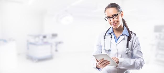 Medico donna che tiene tablet pc davanti alla sala operatoria.