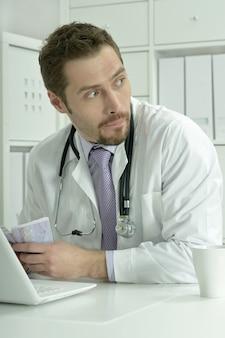 Medico che lavora con laptop e soldi in ufficio