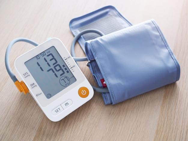 Attrezzature mediche con monitor della pressione sanguigna isolato su un tavolo di legno