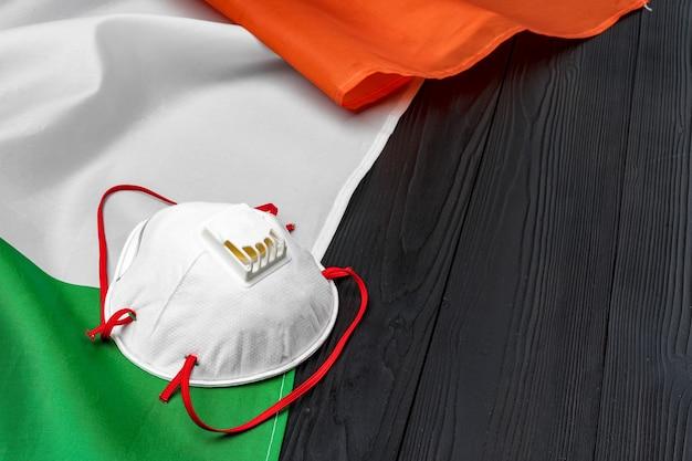 Mascherina medica sulla bandiera dell'italia