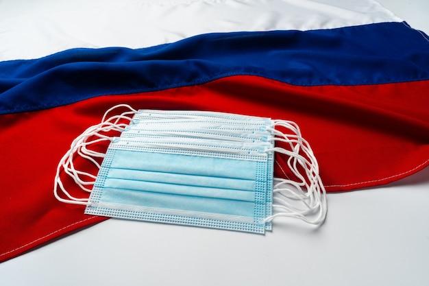 Maschere per il viso mediche sulla bandiera della russia si chiudono