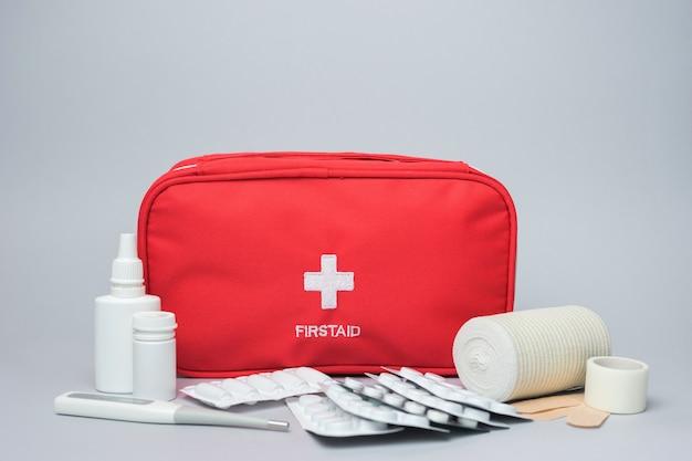 Kit di pronto soccorso medico con medicine e pillole. isolato su sfondo grigio borsa rossa con attrezzature mediche e farmaci per le emergenze.