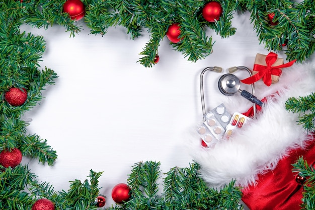 Piatto medico con pillole, confezione regalo, stetoscopio e albero di natale su bianco