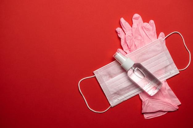Maschera chirurgica per guanti medici, gel disinfettante. attrezzatura di protezione da virus su fondo rosso. concetto medico di patogeno respiratorio coronavirus respiratorio cina 2019-ncov