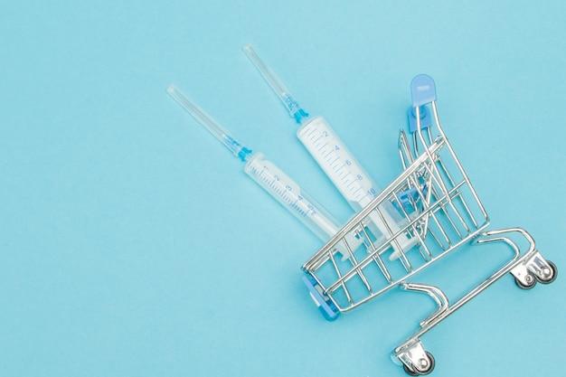 Iniezione medica nel carrello della spesa su sfondo blu.