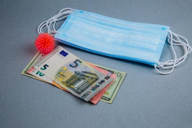 Maschera medica, modello astratto del virus e soldi su un gray.