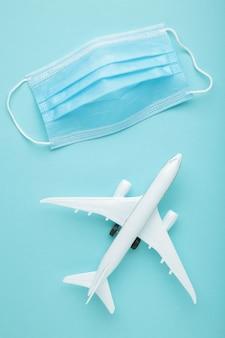 Maschera medica contro il coronavirus con aereo su sfondo blu. concetto di viaggio. vista dall'alto