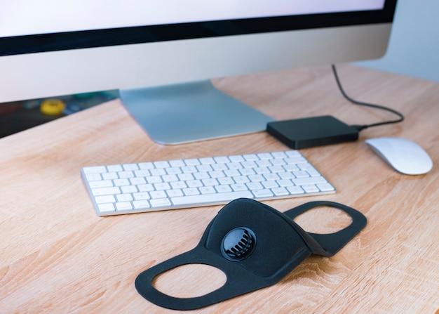 Maschera medica sulla scrivania. lavora e studia da remoto. telelavoro, libero professionista.