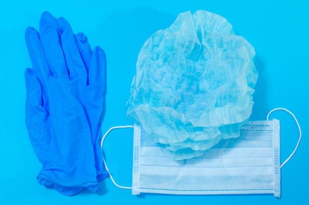 Guanti e cappello della maschera medica su un fondo blu