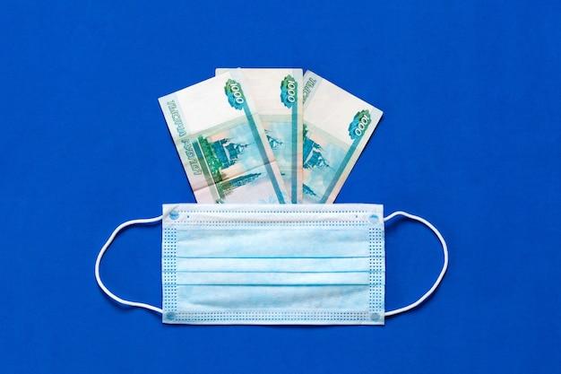 La maschera medica si trova sui soldi. il concetto di aumento del prezzo delle maschere mediche. maschera medica e denaro russo su sfondo blu. mascherina per il coronavirus