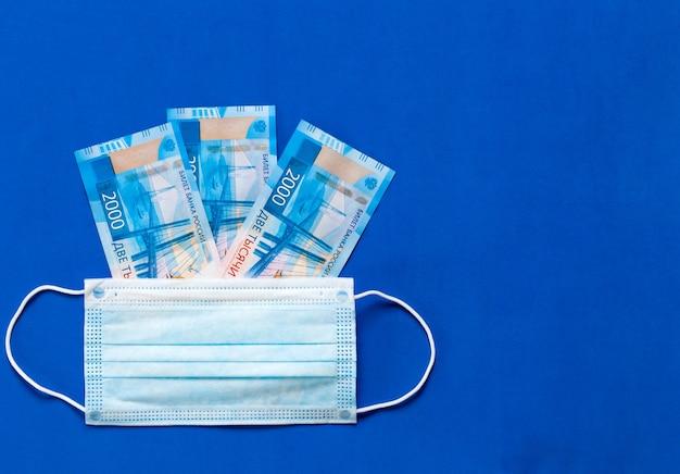 La maschera medica si trova sui soldi. il concetto di aumento del prezzo delle maschere mediche. maschera medica e denaro russo su sfondo blu. mascherina per il coronavirus Foto Premium
