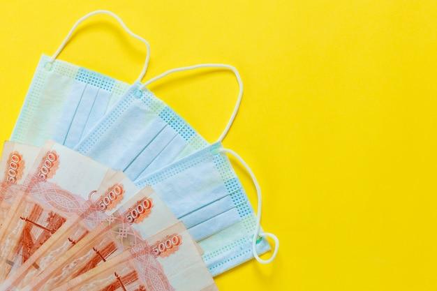 La maschera medica si trova sui soldi. il concetto di aumento del prezzo delle maschere mediche. maschera medica e denaro russo su sfondo giallo.maschera di coronovirus