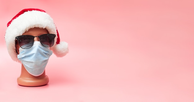 Maschera medica su un manichino e un cappello di capodanno natale 2021 su uno sfondo rosa