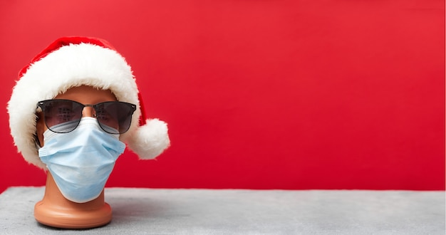 Maschera medica su un manichino e un cappello di capodanno natale 2021 su sfondo rosso