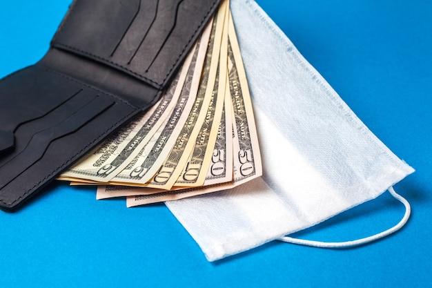 Maschera medica e soldi. visiera medica sul denaro americano. concetto di crisi finanziaria