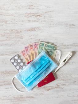 Una maschera medica, pillole, passaporto e denaro sono disposti sul tavolo. concetto di viaggio