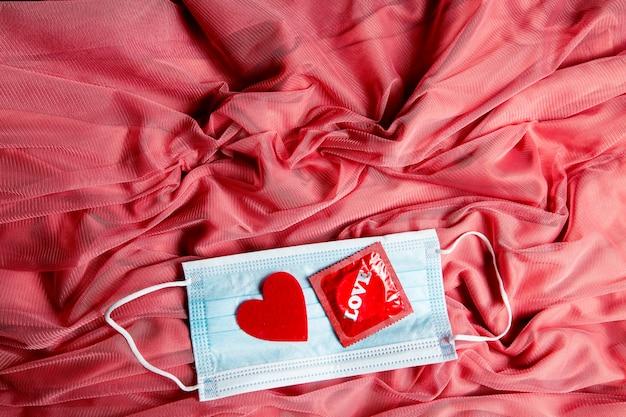 Maschera medica, cuore rosso e preservativo su tessuto di tulle rosa
