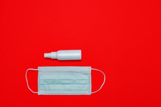 Maschera medica e disinfettante sulla parete rossa. rimanere a casa concetto igienico di quarantena. vista piana, vista dall'alto
