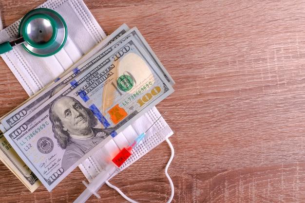 Maschera medica, siringa, stetoscopio e banconote da cento dollari si trova sul tavolo.