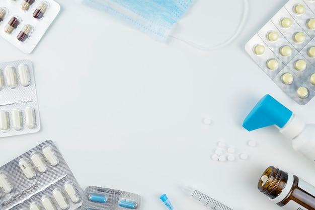 Maschera e compresse mediche su fondo bianco con lo spazio del testo. protezione. epidemia di coronavirus. vista dall'alto