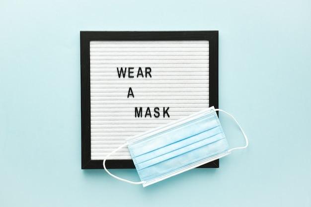 Una maschera medica e un messaggio di testo su un pannello di feltro vengono messi sulla maschera su uno sfondo azzurro. poster, protezione antivirus banner. uno spazio vuoto.