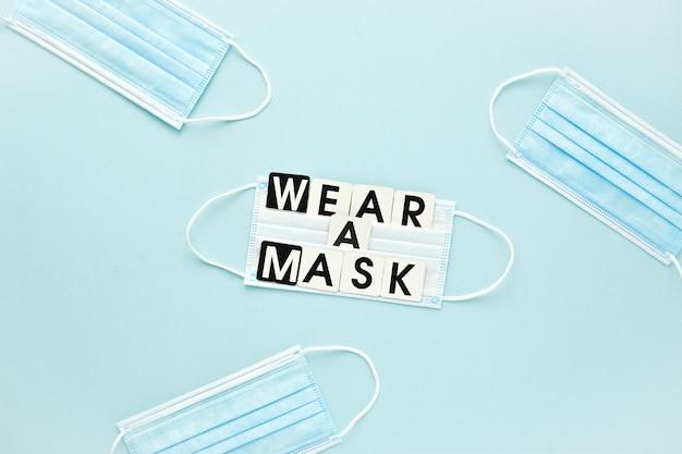 Una maschera medica e un messaggio di testo indossano una maschera su uno sfondo azzurro. poster, protezione antivirus banner. uno spazio vuoto.