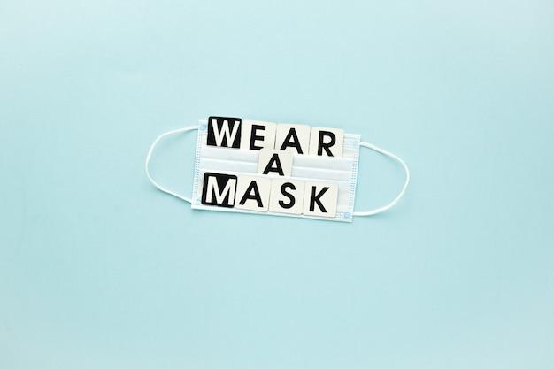 Una maschera medica e un messaggio di testo indossano una maschera su uno sfondo azzurro poster banner virus prote