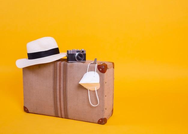 Maschera medica, viaggio, aeroplani, valigia, macchina fotografica, sfondo giallo, problemi di viaggio con covid-19