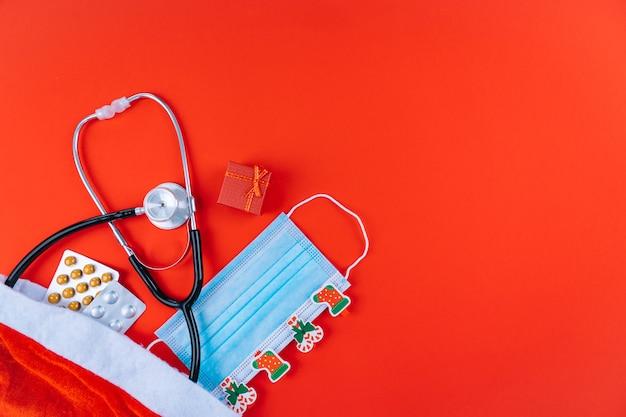Maschera medica con adesivi chrismtas, stetoscopio e farmaci