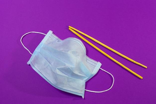 Maschera medica e bacchette di legno su sfondo viola