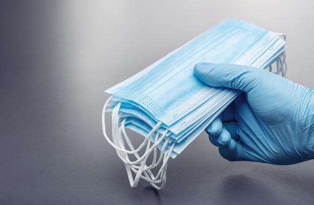Maschere mediche in mano maschio che indossa guanto di gomma blu. studio shot, copia dello spazio.