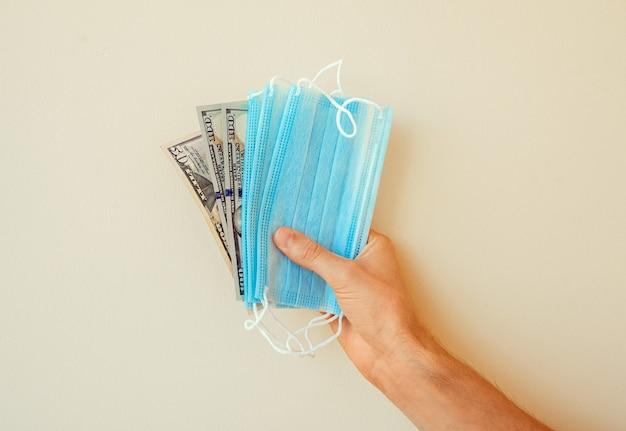 Maschere mediche e denaro nella mano di un uomo su uno sfondo solido. banconote da cento dollari